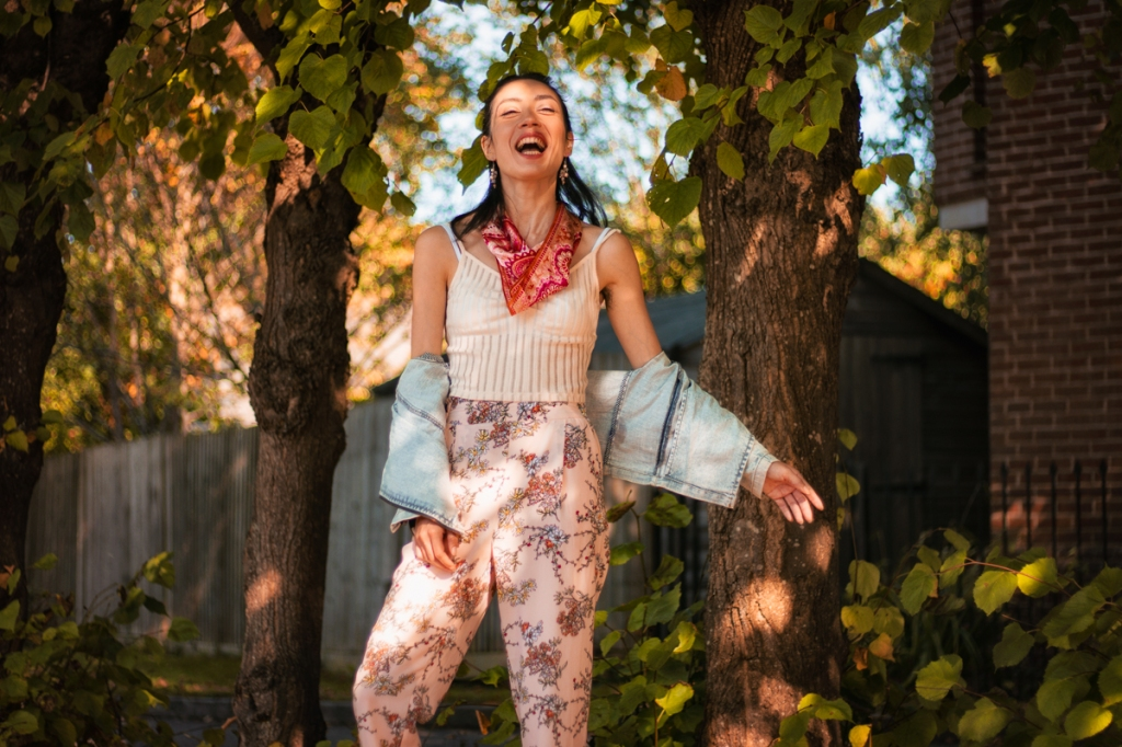 woman in casual summer clothes laughing and carefree on leafy suburban street